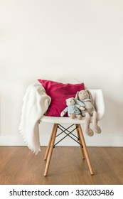 Image of white baby blanket and toy on chair