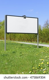 Image of a white blank board on a meadow with blue sky