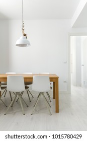 Image of a white interior with a lamp and a wooden table.