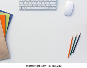 Image of White Office Desk with Computer Keyboard Mouse Color Pencils Booklets and other Supplies Top View