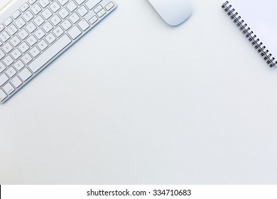 Image of White Office Desk with Computer Keyboard Mouse and Notepad from above