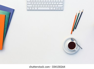 Image of White Office Table with Computer Keyboard Color Pencils Booklets Coffee Mug and other Supplies Top View