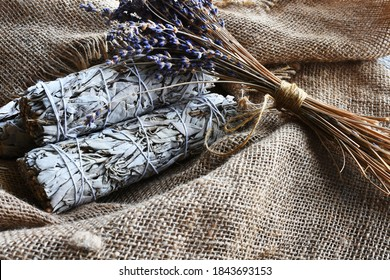 An image of white sage smudge sticks and dried lavender flowers on vintage burlap cloth.
