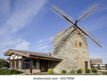 image of a windmill building over a blue sky