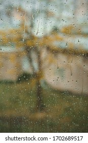 An image in a window covered with rain drops