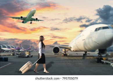 Image of woman in airport looking at taking off airplane, business