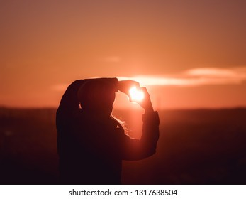 Image of woman from behind forming a heart with her hands with sun shining towards her face