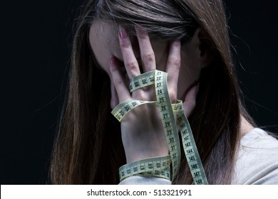 Image of a woman covering her face with a centimeter, dark background