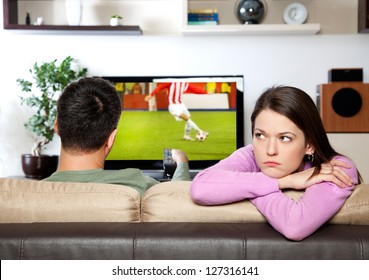 Image of woman getting bored, while her partner watching sports I am the author of image on TV screen