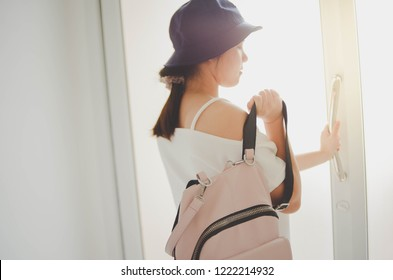 image of a woman getting ready for a travel trip by wearing a backpack and a hat. background of a door.