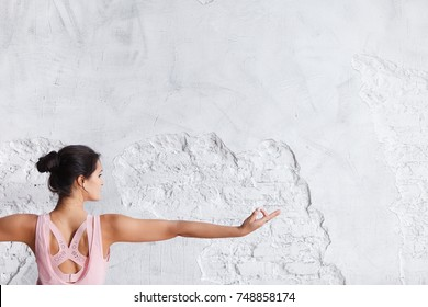 Image of woman hand in prana mudra. Gesture is on white brick wall background.. Yoga and healthy lifestyle concept