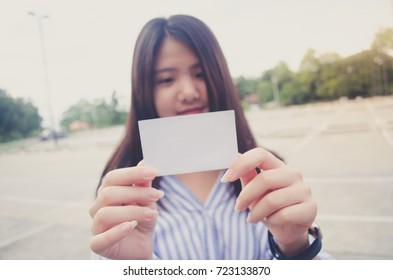 Image of a woman holding a blank piece of paper or card in white and she is smiling. Yellow flare. The background is a outdoor parking lot and concrete floor and tree.