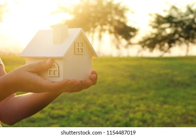 Image of woman holding small wooden house outdoors at sunset light