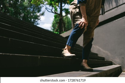 Image of a woman holds her leg while walking down on stairs. Pain and suffering from Patellar Tendonitis, Medical symptom concept.