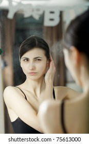 An image of a woman looking at herself in the mirror