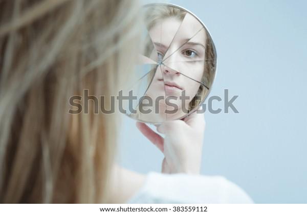 Imagen de mujer con trastorno mental sosteniendo un espejo roto