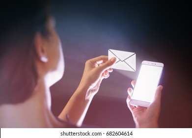 Image of a woman with a smartphone in her  hand. She receives an email. Online mail, correspondence, feedback, reporting, communication.