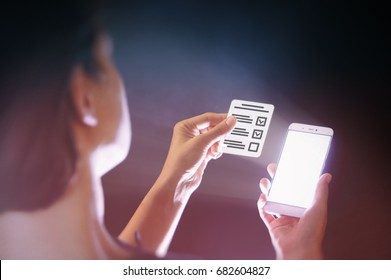 Image of a woman with a smartphone in her  hand. She holds a questionnaire. Modern methods of questioning, voting, examining, testing, etc.