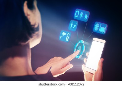 Image of a woman with a smartphone in her  hand. She with the help of touches controls all the parameters of a smart house.