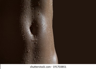 An image of a woman's abs and naval with water drops on the skin.