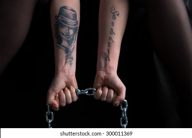 Image of woman's hands holding chain on black background