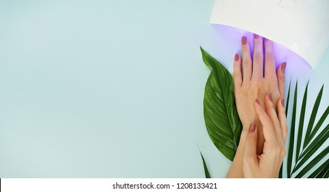 image of woman's manicure and led lamp on blue background