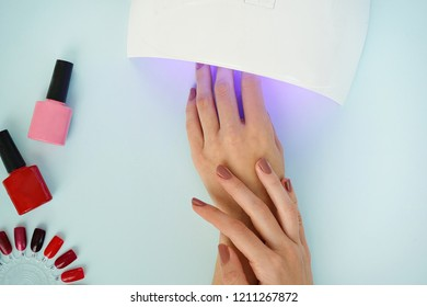 image of woman's manicure and manicure tools on blue background