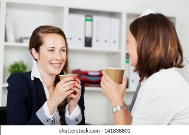 Image of women executives sipping coffee and having an interesting conversation during a break.