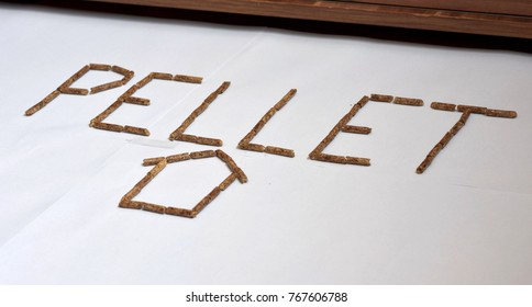 Image of wood pellet grains forming letters and home icon isolated on white background