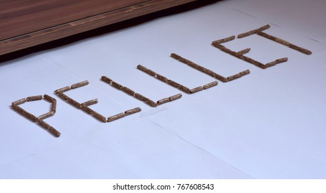 Image of wood pellet grains forming letters isolated on white background