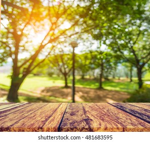 image of wood table and blur green tree background.