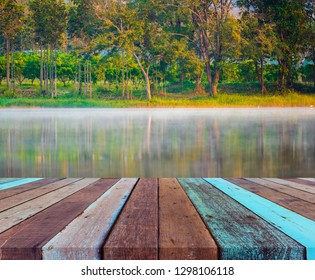 image of wood table and fog on the water surface in the morning in the pond, there is a forest, a backdrop of warm sunny days.
