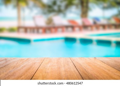 Image of wood table in front of a swimming pool blurred background. Brown wooden desk empty counter in front of the poolside on beautiful beach resort and outdoor spa.