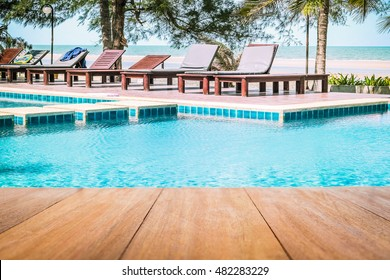 Image of wood table in front of a swimming pool background. Brown wooden desk empty counter in front of the poolside on beautiful beach resort and outdoor spa vacation day.