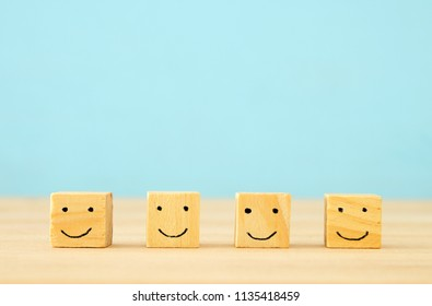 image of  wooden blocks with smiling faces icons over  table ,building a strong team, human resources and management concept.