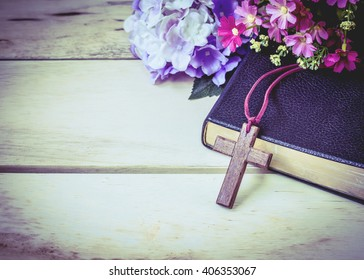 image of the wooden cross and black bible with flowers on wooden background