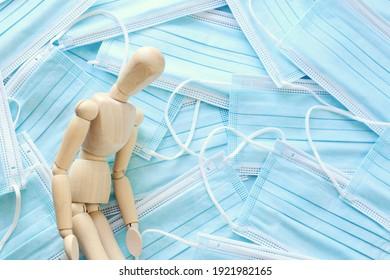 Bild der Holzpuppe mit beunruhigten Stressgedanken. auf Schutzmaske-Hintergrund. Ängstlichkeit und Überlast während der Covid-19-Coronavirus-Pandemie
