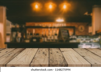 Image of wooden table in front of abstract blurred background of cafe lights