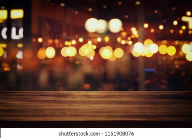 Image of wooden table in front of abstract blurred restaurant lights background