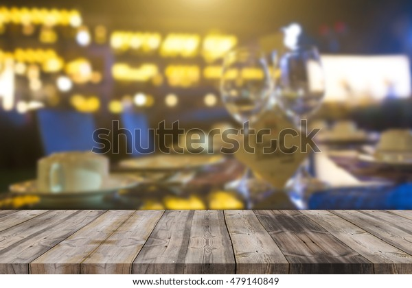 image of wooden table in front of abstract blurred background of resturant lights can be used for montage or display your products