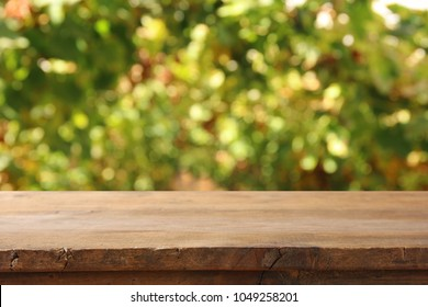 Image of wooden table in front of blurred vineyard landscape at sun light. Ready for product display montage
