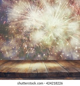 image of wooden table in front of blurred fireworks background