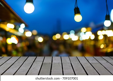 Image of wooden table in front of decorative outdoor string lights hanging on electricity post with blur people. festival and holiday concepts, can used for display or montage your products.