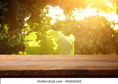 image of wooden table in front of vineyard landscape at sunset light. vintage filtered