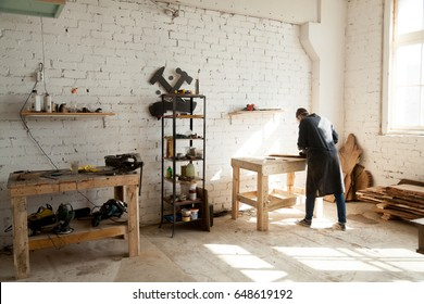 Image of woodworking workshop with electric instruments on shelves, joiner working at workbench, dried wooden materials on floor. Cabinet maker or artisan works in bright carpentry shop on new project