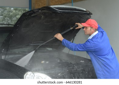 image of worker cleaning the cars engine with a karcher