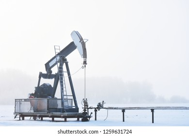 An image of a working oil producing pump jack on a cold and foggy winter day.