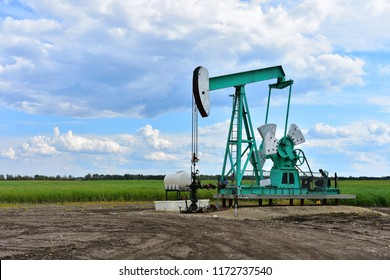 An image of a working oil well pump jack on a cloudy day.