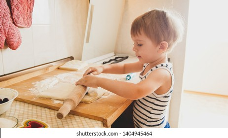 Image years old toddler boy rolling dough on wooden board and baking cookies for breakfast. Child cooking on kitchen. Smart kids