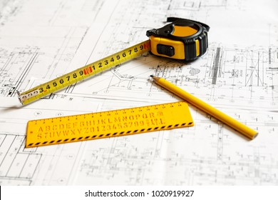 Image of a yellow ruler, yellow pencil and a collapsible ruler on architecture blueprint plan. Architect working concept